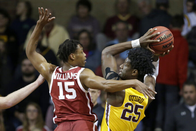 Minnesota's Daniel Oturu (25) is defended by Oklahoma's Alondes Williams (15) during the first half of an NCAA college basketball game in Sioux Falls, S.D., Saturday, Nov. 9, 2019. (AP Photo/Nati Harnik)