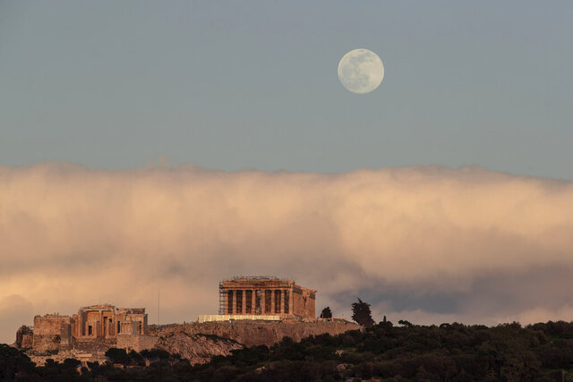 The moon rises behind the ancient Acropolis hill with the 500 BC Parthenon temple in Athens, on Saturday, Feb. 8, 2020. (AP Photo/Petros Giannakouris)
