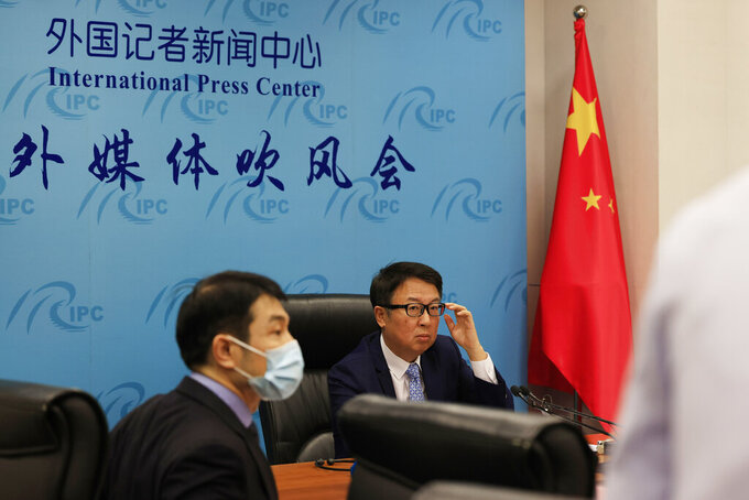"""Director of the Chinese Foreign Ministry's Africa Department, Wu Peng, center right, prepares for a briefing in Beijing on Thursday, May 20, 2021. Wu told reporters on Thursday that China is currently providing COVID-19 vaccines to nearly 40 African countries and that the vaccines were either being donated or sold at """"favorable prices."""" (AP Photo/Ng Han Guan)"""