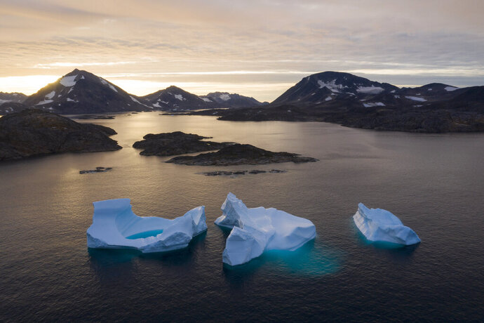 In this Aug. 16, 2019, photo, large Icebergs float away as the sun rises near Kulusuk, Greenland. Scientists are hard at work, trying to understand the alarmingly rapid melting of the ice. (AP Photo/Felipe Dana)