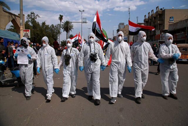 FILE - In this March 1, 2020 file photo, anti-government protesters wear hazmat-like suits and gas masks during a rally in Baghdad, Iraq. As 2019 gave way to 2020 in a cloud of tear gas, and in some cases a hail of bullets, from Hong Kong to Baghdad, from Beirut to Barcelona and Santiago, it seemed civil disobedience and government crackdowns on protests would dominate the international landscape. Then came the coronavirus. But some protesters are trying to keep their movements alive, adjusting to the outbreak fears. The vast majority of people recover from the new coronavirus. (AP Photo/Khalid Mohammed, File)