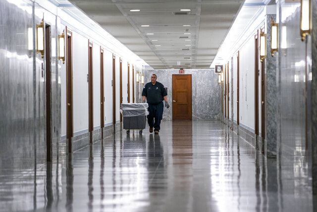 A workman walks through the empty corridors of the Dirksen Senate Office Building on Capitol Hill as lawmakers negotiate on the emergency coronavirus response legislation, in Washington, Wednesday, March 18, 2020. (AP Photo/J. Scott Applewhite)