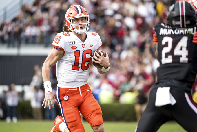 Clemson quarterback Trevor Lawrence (16) carries the ball against South Carolina during the first half of an NCAA college football game Saturday, Nov. 30, 2019, in Columbia, S.C. (AP Photo/Sean Rayford)