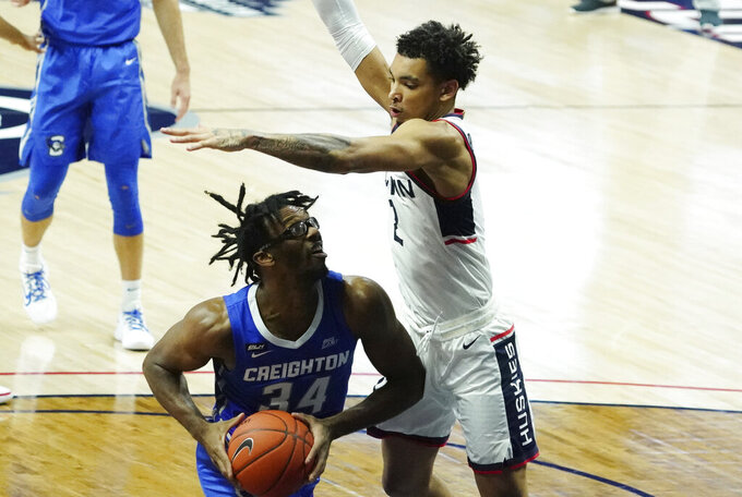 Connecticut guard James Bouknight (2) pressures Creighton guard Denzel Mahoney (34) in the first half of an NCAA college basketball game in Storrs, Conn., Sunday, Dec. 20, 2020. (David Butler II/Pool Photo via AP)