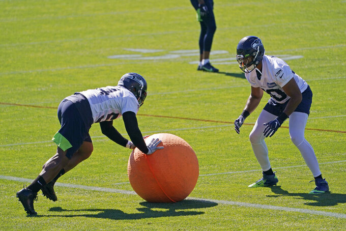 Seattle Seahawks linebacker Bobby Wagner, left, rolls a weighted ball with linebacker K.J. Wright, right, during NFL football training camp Tuesday, Sept. 1, 2020, in Renton, Wash. (AP Photo/Ted S. Warren)