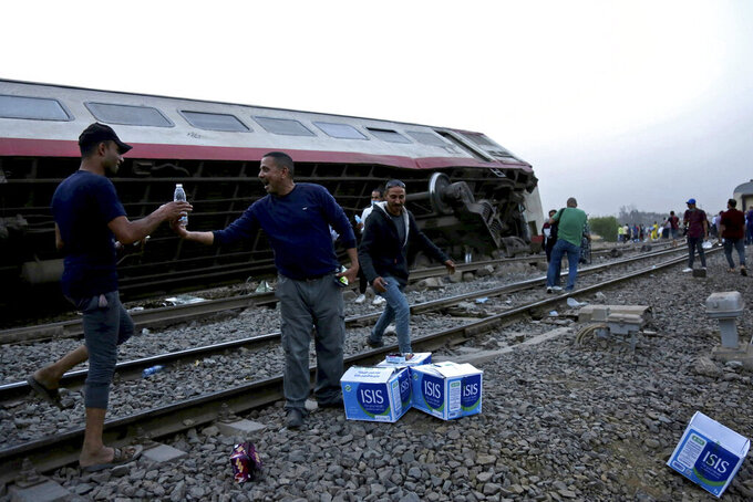 People break their fast during the holy month of Ramadan, at the site of a passenger train that derailed injuring around 100 people, near Banha, Qalyubia province, Egypt, Sunday, April 18, 2021. The train was travelling to the Nile Delta city of Mansoura from the Egyptian capital, the statement said. (AP Photo/Fadel Dawood)