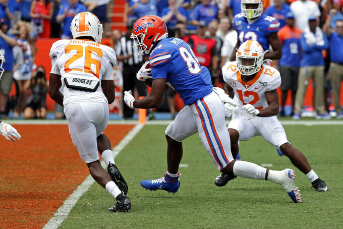 Florida tight end Kyle Pitts, center, runs past Tennessee defensive back Theo Jackson (26) and defensive back Shawn Shamburger (12) for a touchdown on a 19-yard pass play during the first half of an NCAA college football game, Saturday, Sept. 21, 2019, in Gainesville, Fla. (AP Photo/John Raoux)