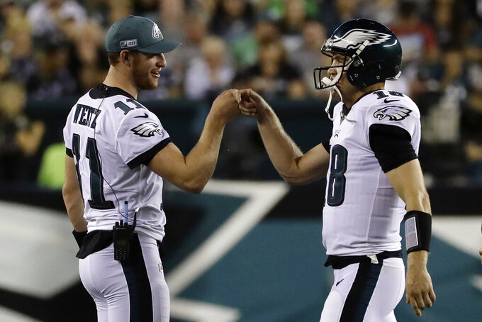 Philadelphia Eagles' Carson Wentz, left, reacts with Josh McCown during the first half of a preseason NFL football game against the Baltimore Ravens, Thursday, Aug. 22, 2019, in Philadelphia. (AP Photo/Michael Perez)