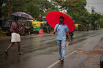 People wearing masks as precaution against the coronavirus walk holding umbrellas during monsoon rains in Kochi, Kerala state, India, Saturday, June 6, 2020. India which surpasses Italy as the sixth worst-hit by the coronavirus caseload is trying to contain the chain of transmission while allowing social and economic activity to resume. (AP Photo/ R S Iyer)