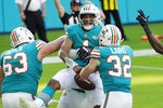 Miami Dolphins offensive guard Michael Deiter (63) and running back Patrick Laird (32) celebrate a touchdown by quarterback Tua Tagovailoa (1), center, during the second half of an NFL football game against the New England Patriots, Sunday, Dec. 20, 2020, in Miami Gardens, Fla. (AP Photo/Chris O'Meara)