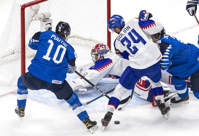 Finland's Kasper Puutio (10) is stopped by Slovakia's goalie Samuel Hlavaj and Andrej Golian (24) during the first period of a match at the IIHF World Junior Hockey Championships in Edmonton, Alberta, on Wednesday, Dec. 30, 2020.(Jason Franson/The Canadian Press via AP)