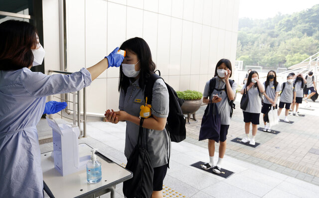 Students wearing face masks to help protect against the spread of the new coronavirus stand in a line to have their body temperatures checked before entering their classrooms at a middle school in Chungju, South Korea, Monday, June 8, 2020. (In Jin-hyun/Newsis via AP)