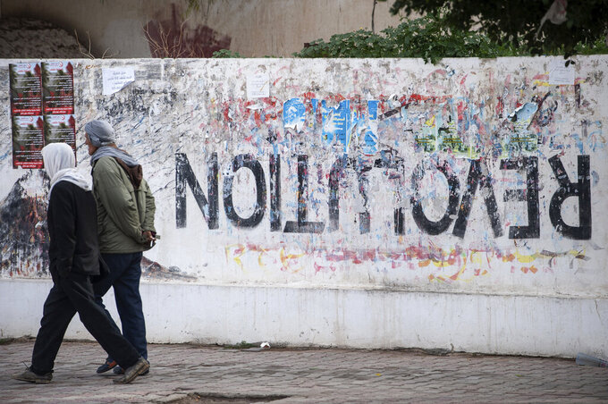 Residents walk past graffiti in Sidi Bouzid, Tunisia, Friday, Dec. 11, 2020. Hundreds of desperate Tunisians have set themselves on fire in the past 10 years in an act of protest, following the example of 26-year-old fruit seller Mohammed Bouazizi, whose self-immolation in 2010 led to the downfall of Tunisia's dictator of 23 years. His public suicide unleashed the Arab Spring uprisings and a decade of crackdowns and civil wars across the region. (AP Photo/Riadh Dridi)