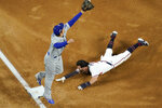 Atlanta Braves' Dansby Swanson is safe at third past Los Angeles Dodgers shortstop Corey Seager on a single by Nick Markakis during the second inning in Game 5 of a baseball National League Championship Series Friday, Oct. 16, 2020, in Arlington, Texas. (AP Photo/David J. Phillip)