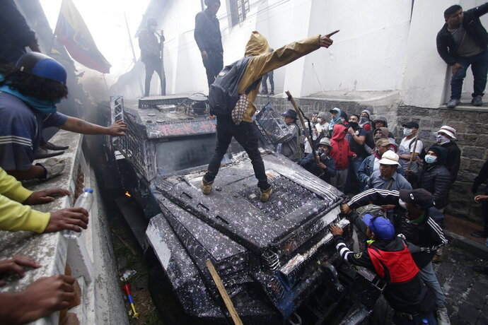 In this Oct. 9, 2019 photo, anti-government demonstrators commandeer an armored vehicle during a nationwide strike against President Lenin Moreno and his economic policies in Quito, Ecuador. The military warned people who plan to participate in the national strike over fuel price hikes to avoid acts of violence. (AP Photo/Carlos Noriega)