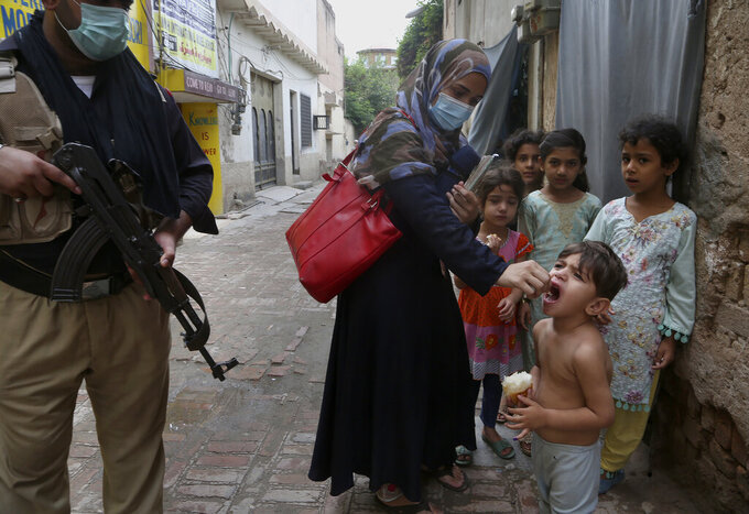 A police officer stand guard while a health worker administers a polio vaccine to a child in Peshawar, Pakistan, Friday, July 30, 2021. The Pakistani government launched an anti-polio vaccination campaign in an effort to eradicate the crippling disease. (AP Photo/Muhammad Sajjad)