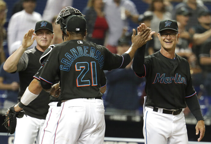 Miami Marlins manager Don Mattingly, right, high-fives Curtis Granderson after they defeated the Washington Nationals in a baseball game, Friday, April 19, 2019, in Miami. (AP Photo/Lynne Sladky)
