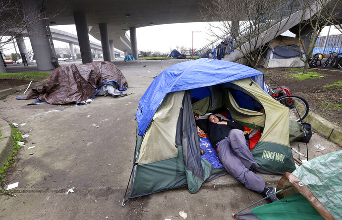 FILE - In this Feb. 9, 2016 file photo, a man lies in a tent with others camped nearby under and near an overpass in Seattle. Microsoft has pledged another $250 million to address homelessness and develop affordable housing in response to the Seattle region's widening affordability gap. (AP Photo/Elaine Thompson, File)