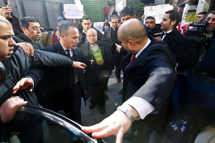 Archbishop Charles Scicluna, center left, and Monsignor Jordi Bertomeu, center right, are protected by security guards as university students demand that the Catholic church investigate cases of sexual abuses inside the Catholic University of Chile, after a press conference at that same University in Santiago, Chile, Wednesday, June 13, 2018. Scicluna and Bertomeu, the investigators of sex abuse in Chile's church, returned to Chile to begin what the Vatican has said is a