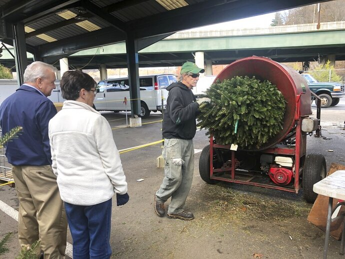 In this Wednesday, Dec. 4, 2019 photo, Bob and Jane Atkins, left, of Madison, W.Va., watch Robert Cole of French Creek Farms place their Christmas tree into a wrapping machine before being loaded onto their vehicle at the Capitol Market in Charleston, W.Va. Bob Atkins said not only are Christmas tree prices higher this year, but