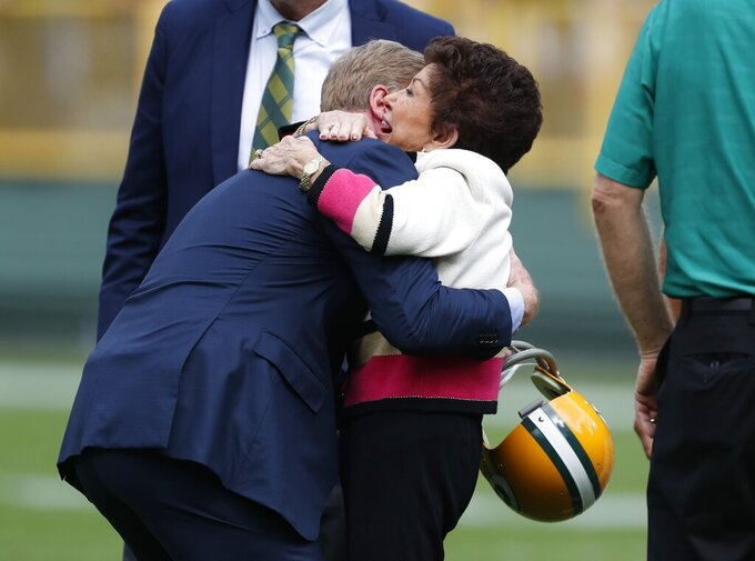 Cherry Louise Morton, wife of former Green Bay Packers Bart Starr, is hugged by NFL Commissioner Roger Goodell during halftime of an NFL football game between the Green Bay Packers and the Minnesota Vikings Sunday, Sept. 15, 2019, in Green Bay, Wis. (AP Photo/Matt Ludtke)
