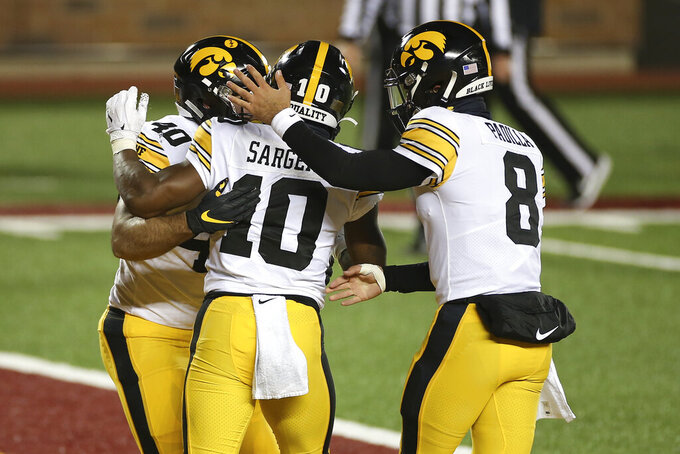 Iowa running back Mekhi Sargent (10) celebrates with fullback Turner Pallissard (40) and quarterback Alex Padilla (8) after Sargent's touchdown against Minnesota during the second half of an NCAA college football game Friday, Nov. 13, 2020, in Minneapolis. Iowa won 35-7. (AP Photo/Stacy Bengs)