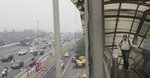A commuter wars a pollution mask and crosses a foot over bridge with city enveloped in thick layer of smog in New Delhi, India, Thursday, Nov. 14, 2019. Schools in India's capital have been shut for Thursday and Friday after air quality plunged to a severe category for the third consecutive day, enveloping New Delhi in a thick gray haze of noxious air. (AP Photo/Manish Swarup)