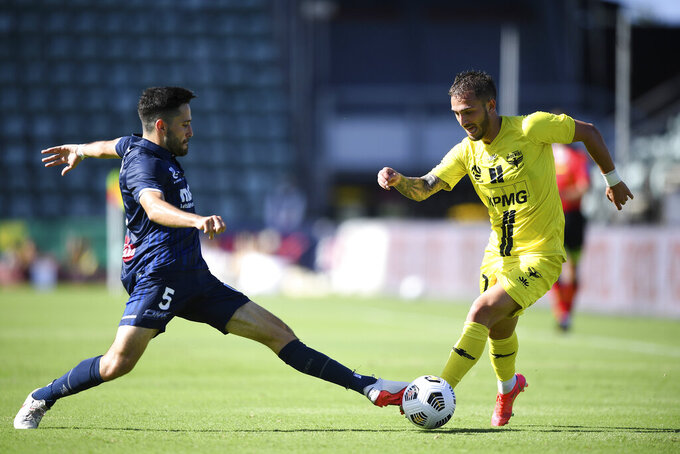 Stefan Nigro, left, of the Mariners tackles Reno Piscopo of the Wellington Phoenix during their A-League match in Wollongong, Australia on Feb. 14, 2021. The A-League announced Friday, April 30, 2021, that the Phoenix, fighting for a playoff spot, will play a home match in the New Zealand capital of Wellington on May 22. (Joel Carrett/AAP Image via AP)