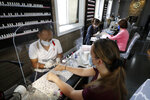 Nail technician Minh Pham, left, wears gloves, a mask, and works behind a plastic shield out of concern for the coronavirus as he performs a manicure on Jolie O'Neil, front right, Monday, June 22, 2020, at a nail salon, in Mansfield, Mass. Nail salons are one of the businesses open to the public as Massachusetts begins phase two of its planned reopening during the coronavirus pandemic. (AP Photo/Steven Senne)
