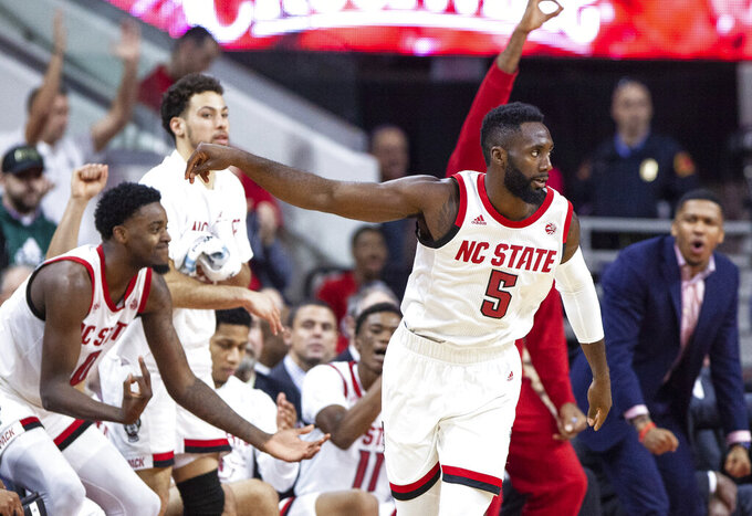 North Carolina State's Eric Lockett (5) holds his follow-through after hitting a shot three-point basket during the second half of an NCAA college basketball game against Clemson in Raleigh, N.C., Saturday, Jan. 26, 2019. (AP Photo/Ben McKeown)