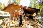 Dan Santos sprays water while defending his girlfriend's Greenville home as the Dixie Fire burns nearby in Plumas County, Calif., on Tuesday, Aug. 3, 2021. Dry and windy conditions have led to increased fire activity as firefighters battle the blaze which ignited July 14. (AP Photo/Noah Berger)
