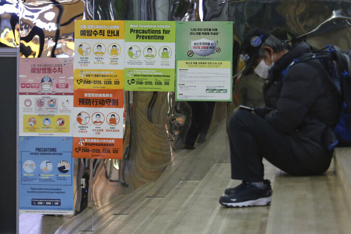 Posters on precautions against the coronavirus are displayed at a subway station in Seoul, South Korea, Tuesday, Nov. 24, 2020. The signs on posters read