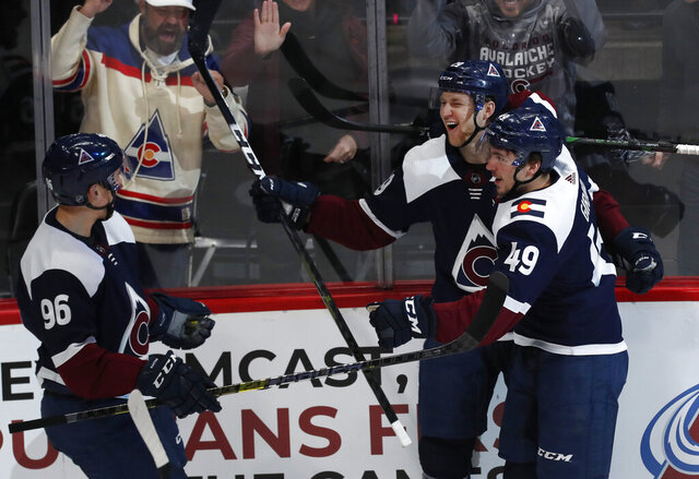 Colorado Avalanche center Nathan MacKinnon, center, celebrates scoring a goal with defenseman Samuel Girard, right, and right wing Mikko Rantanen in the first period of an NHL hockey game against the St. Louis Blues Saturday, Jan. 18, 2020, in Denver. (AP Photo/David Zalubowski)