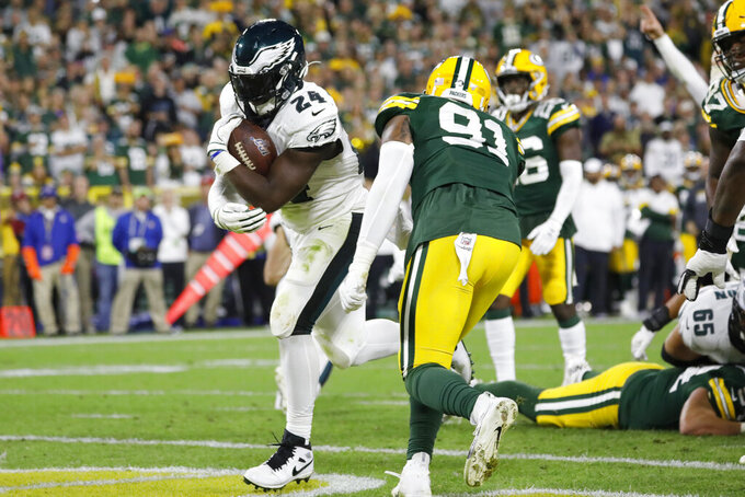 Philadelphia Eagles running back Jordan Howard rushes for a touchdown past Green Bay Packers outside linebacker Preston Smith (91) during the first half of an NFL football game Thursday, Sept. 26, 2019, in Green Bay, Wis. (AP Photo/Jeffrey Phelps)