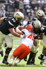 Purdue offensive linemen Gus Hartwig (53) and Spencer Holstege (75) block Illinois linebacker Shammond Cooper (40) during the first quarter of an NCAA college football game, Saturday, Sept. 25, 2021, in West Lafayette, Ind. (Nikos Frazier/Journal & Courier via AP)