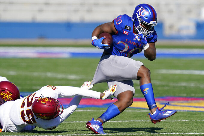 Kansas running back Daniel Hishaw Jr. (20) is slowed by Iowa State defensive back T.J. Tampa (25) during the second half of an NCAA college football game in Lawrence, Kan., Saturday, Oct. 31, 2020. (AP Photo/Orlin Wagner)