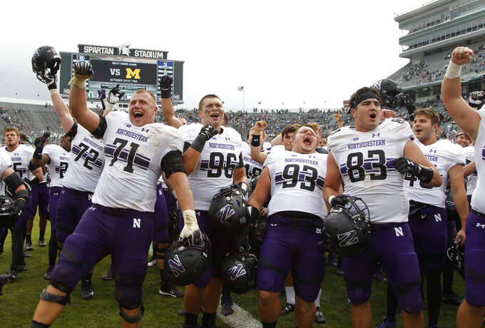 Northwestern players, including Tommy Doles (71), Trevor Kent (96), Joe Spivak (93) and Will Lansbury (83), celebrate an NCAA college football game against Michigan State, Saturday, Oct. 6, 2018, in East Lansing, Mich. Northwestern won 29-19. (AP Photo/Al Goldis)