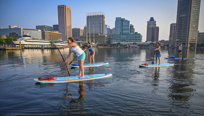 Stand-up paddlesboard company B'More SUP instructor Emily Knaus, left, leads a group on a tour of Baltimore's Inner Harbor Wednesday morning, July 21, 2021. (Jerry Jackson/The Baltimore Sun via AP)