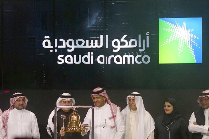 FILE - In this Dec. 11, 2019, file photo, Saudi Arabia's state-owned oil company Aramco and stock market officials celebrate the debut of Aramco's initial public offering on the Riyadh Stock Market, in Riyadh, Saudi Arabia. Aramco paid the Saudi government 30% less in taxes in 2020, the company reported Monday, March 22, 2021, as the region's largest economy grapples with the pressures of the coronavirus pandemic and low oil prices. Despite Aramco's steep losses, the company managed to keep its dividend pledge to shareholders by taking on a ballooning amount of debt. (AP Photo/Amr Nabil, File)