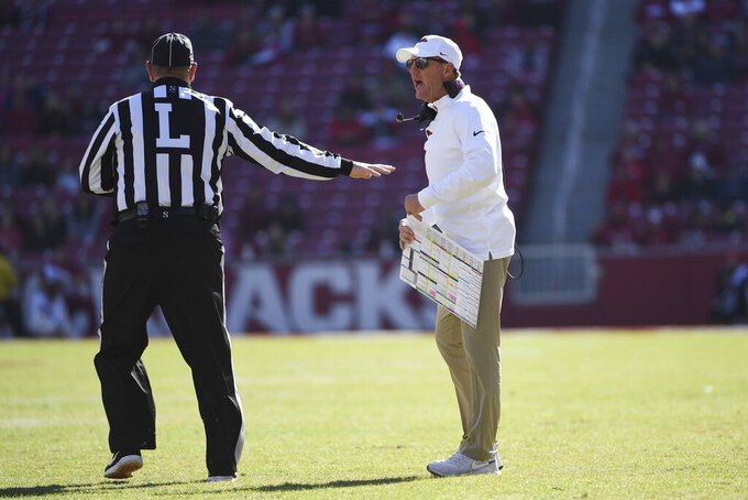 Arkansas coach Chad Morris talks with an official while playing Western Kentucky during the second half of an NCAA college football game, Saturday, Nov. 9, 2019 in Fayetteville, Ark. (AP Photo/Michael Woods)