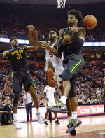 Baylor forward Freddie Gillespie, right, scrambles for a rebound over Texas forward Royce Hamm Jr. (5) during the second half of an NCAA college basketball game, Monday, Feb. 10, 2020, in Austin, Texas. (AP Photo/Eric Gay)