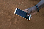 In this Saturday July 6, 2019 photo, Saitoti Petro photographs a lion print near the village of Loibor Siret, Tanzania. Petro is one of more than 50 lion monitors from communities on the Maasai Steppe who walk daily patrol routes to help shepherds guard their livestock in pasture. (AP Photo/Jerome Delay)