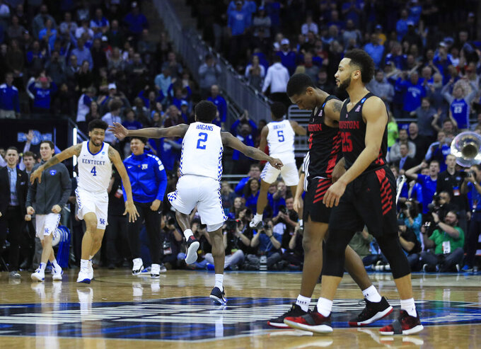 Houston's Galen Robinson Jr. (25) walks off the court as Kentucky celebrates in the background following a men's NCAA tournament college basketball Midwest Regional semifinal game Friday, March 29, 2019, in Kansas City, Mo. (AP Photo/Orlin Wagner)