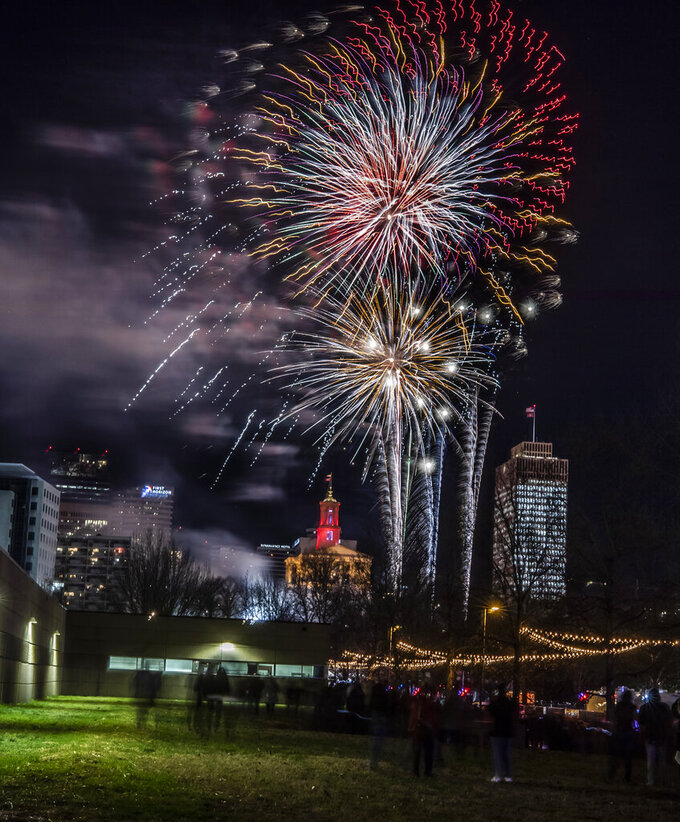 In this Dec. 31, 2019 photo,  fireworks explode over Bicentennial Mall during the Jack Daniel's Music City Midnight New Year's Eve celebration in Nashville, Tenn.  The Christmas morning bombing of the downtown tourist district forced organizers of what was already slated to be a very muted New Year's celebration to dial it back even further. Nashville had already canceled its outdoor public concert for a televised one. But organizers had hoped to blow up a 2020 number and have fireworks as a way to say good riddance to a terrible year. (Alan Poizner/The Tennessean via AP)