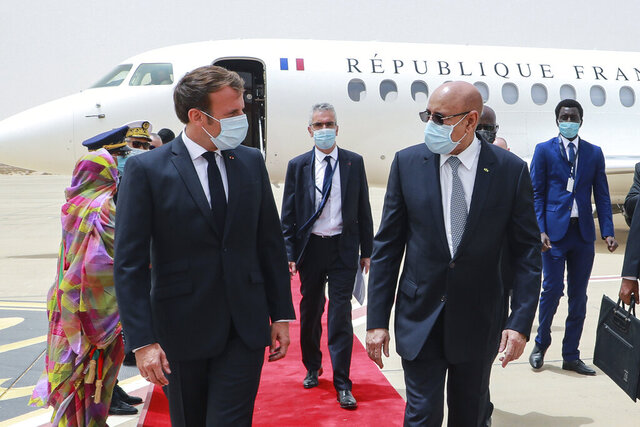 French President Emmanuel Macron, left, is welcomed by Mauritania President Mohamed Ould Ghazouani, right, upon arrival at Nouakchott Oumtounsy International Airport Tuesday June 30, 2020, in Nouakchott, to attend a G5 Sahel summit. Leaders from the five countries of West Africa's Sahel region, Burkina Faso, Chad, Mali, Mauritania and Niger, meet with French President Emmanuel Macron and Spanish Prime Minister Pedro Sanchez in Mauritania's capital Nouakchott on Tuesday to discuss military operations against Islamic extremists in the region, as jihadist attacks mount. The five African countries, known as the G5, have formed a joint military force that is working with France, which has thousands of troops to battle the extremists in the Sahel, the region south of the Sahara Desert. (Ludovic Marin, Pool via AP)
