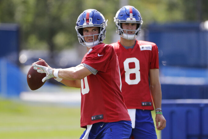 FILE - In this July 25, 2019, file photo, New York Giants' quarterback Eli Manning throws a pass as Daniel Jones watches at the NFL football team's training camp in East Rutherford, N.J. Eli Manning is entering a team-record 16th season with the New York Giants and his career in some ways might be coming full cycle. (AP Photo/Frank Franklin II, File)