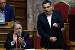Greece's Prime Minister Alexis Tsipras, right, speaks as Greek Alternate Minister of Foreign Affairs George Katrougalos, applauds during a parliament session in Athens, Friday, Feb. 8, 2019. Greek lawmakers are set Friday to approve Macedonia's NATO accession, ending a process to normalize relations between the two neighbors and anchor the country — renamed North Macedonia — firmly within the western sphere of influence. (AP Photo/Thanassis Stavrakis)