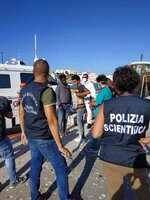 Migrants disembarked from the Open Arms Spanish humanitarian boat arrive in the harbor of the Sicilian island of Lampedusa, southern Italy, Saturday, Aug.17, 2019. Italy's hard-line interior minister buckled under pressure Saturday and agreed to let 27 unaccompanied minors leave a migrant rescue ship after two weeks at sea, temporarily easing a political standoff that has threatened the viability of the populist government. (Concetta Rizzo/ANSA Via AP)