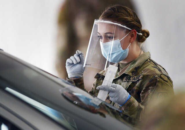 Members of the Illinois National Guard work with the public at the state's new drive-through COVID-19 testing facility at Rolling Meadows High School Friday. The test is self-administered by the person being tested, and the test kits are passed through the partially-opened car window. (Joe Lewnard/Daily Herald via AP)