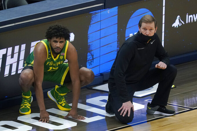 Oregon head coach Dana Altman, right, and guard LJ Figueroa, left, watch from the sideline during the first half of a Sweet 16 game against Southern California in the NCAA men's college basketball tournament at Bankers Life Fieldhouse, Sunday, March 28, 2021, in Indianapolis. (AP Photo/Darron Cummings)
